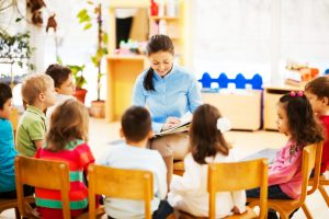 Nursery teacher reading a story to the group of kids. The focus is on the teacher. [url=http://www.istockphoto.com/search/lightbox/9786682][img]http://dl.dropbox.com/u/40117171/children5.jpg[/img][/url] [url=http://www.istockphoto.com/search/lightbox/9786738][img]http://dl.dropbox.com/u/40117171/group.jpg[/img][/url]